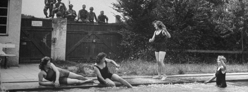 GIs watch German girls swimming in July, 1945 in this image, part of a photo essay for Life magazine.