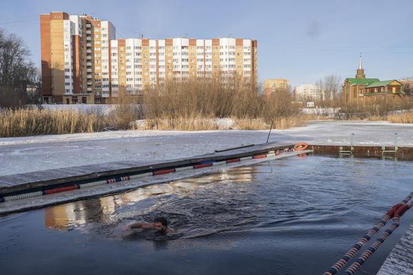Член клуба плавает в проруби на замерзшем озере в Тюмени, чтобы подготовиться к ежегодному соревнованию