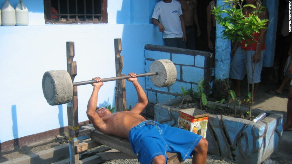 Ninety-five percent of inmates of NBP belong to 12 gangs, according to research by Clarke Jones and Raymund Narag, who took these images in the summer of 2012. Gang culture within the prison often leads to violence, but they say it also fills an important void. Here a prisoner is seen exercising using improvised weights.