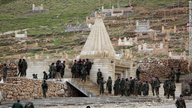 "Kurdish Peshmerga fighters assemble at a shrine on Iraq's Mount Sinjar on Friday, December 19. The Kurdish military said that with the help of coalition airstrikes, it has ""cleansed"" the area of ISIS militants. ISIS has been advancing in Iraq and Syria as it seeks to create an Islamic caliphate in the region."