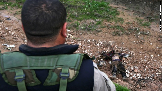 A Peshmerga fighter looks down at the body of an alleged ISIS fighter in Zummar, Iraq, on Thursday, December 18.