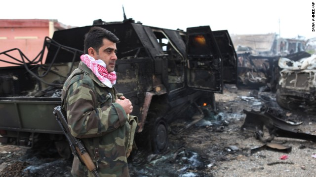 A Kurdish fighter stands next to a destroyed armored vehicle in northern Iraq on December 18. The vehicle was destroyed by an improvised explosive device placed by ISIS militants.