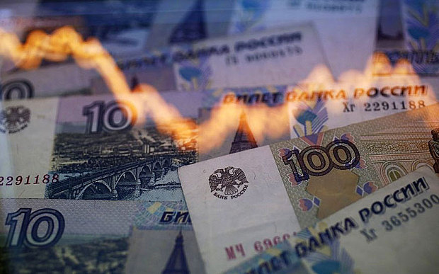 A reflection of a yearly chart of U.S. dollars and Russian roubles are seen on rouble notes in this photo illustration taken in Warsaw