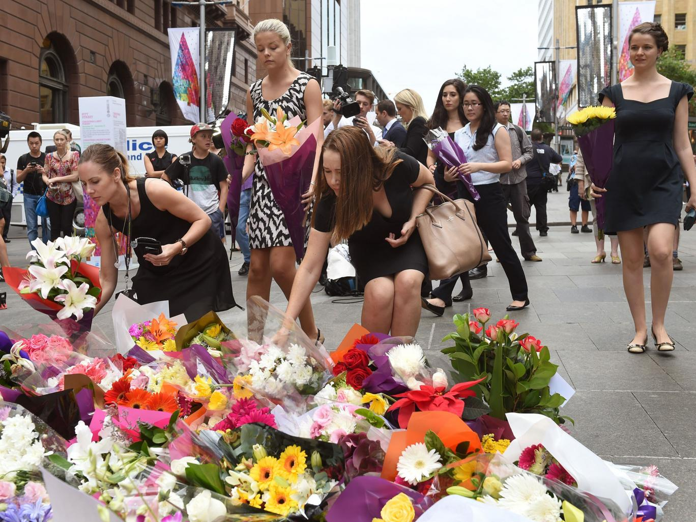 People lay flowers at a floral memorial at the scene of Sydney&;s siege
