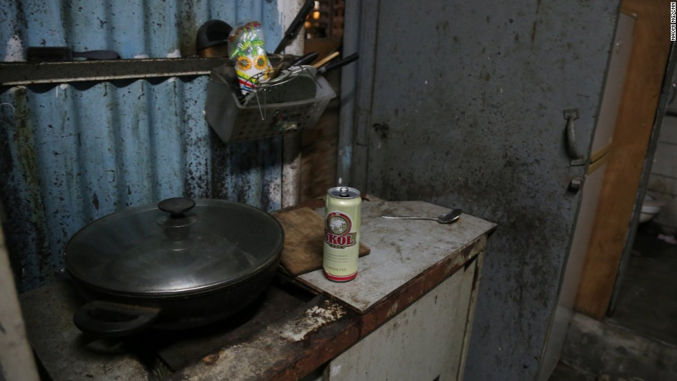 Rooftop dweller, Fung's simple kitchen setup outside his flat is next to his toilet.