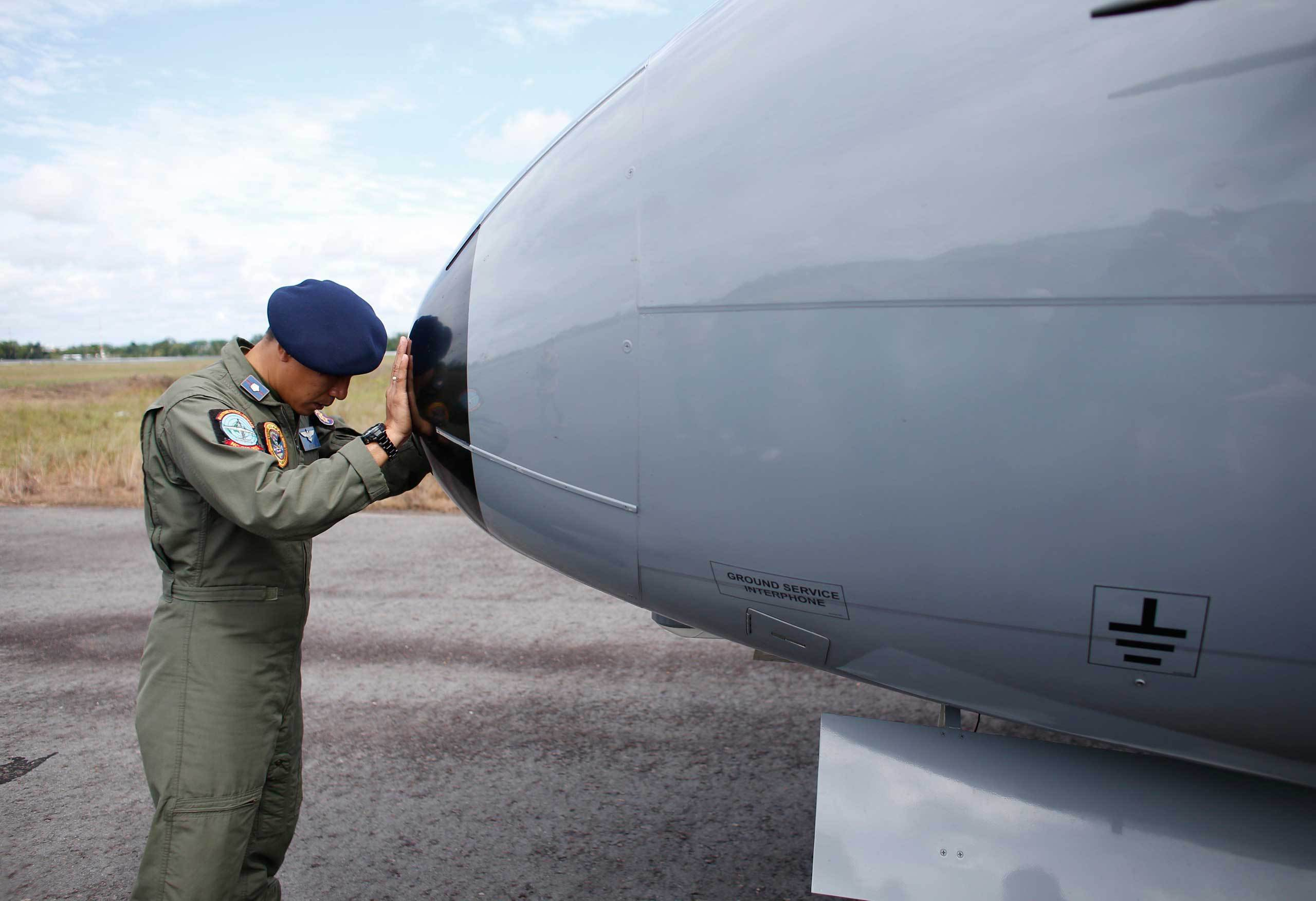 A crew member of an Indonesian Maritime Surveillance plane says a prayer before a search mission to look for AirAsia's Flight QZ8501 in Pangkal Pinang, Bangka Island, Indonesia on Dec. 30, 2014.
