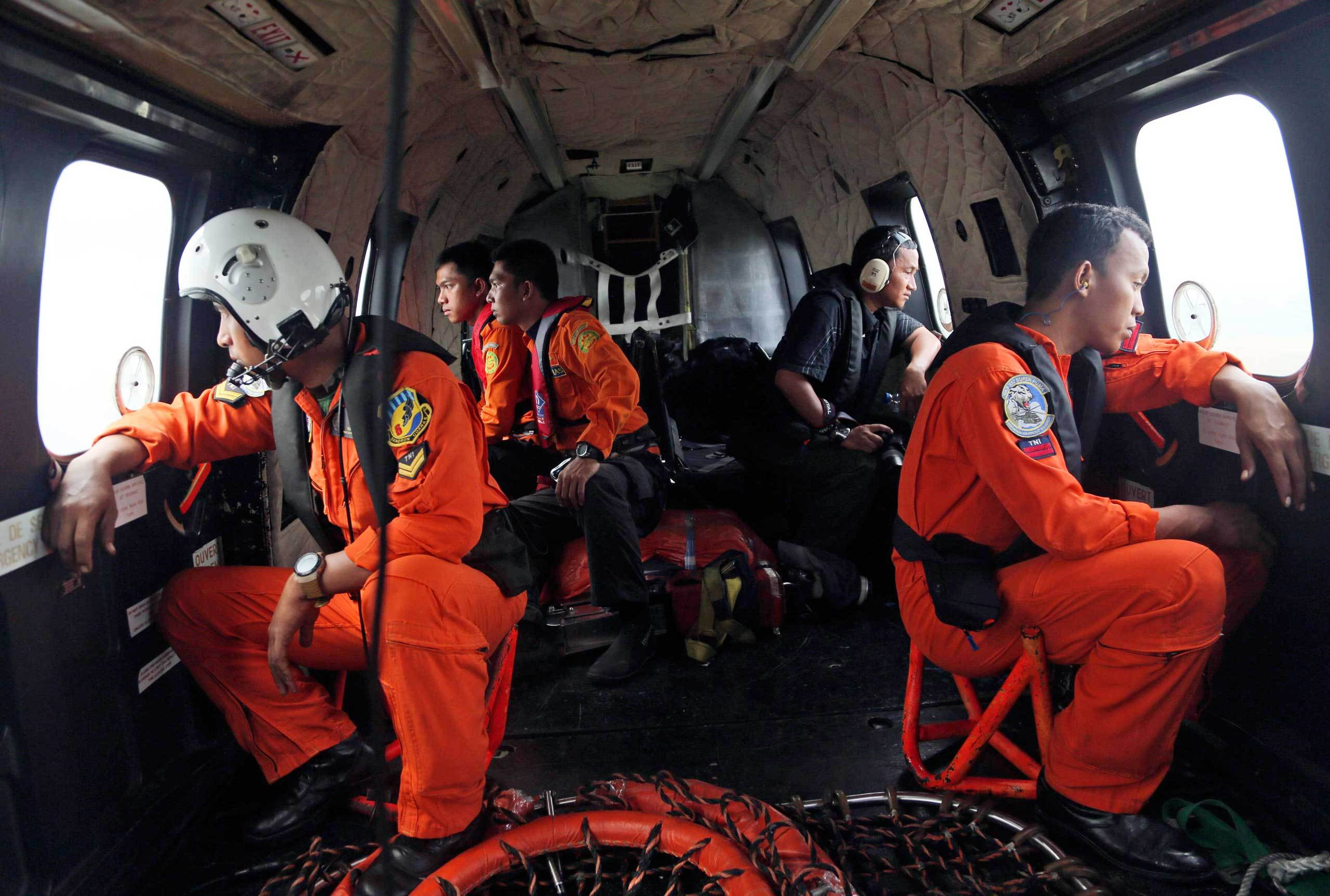 Crewmembers of an Indonesian Air Force NAS 332 Super Puma helicopter look out of the windows during a search operation for the victims and wreckage of AirAsia flight QZ 8501 over the Java Sea