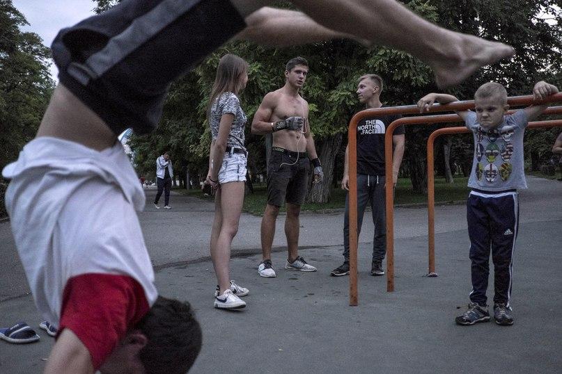 Молодые парни и девушки демонстрируют свою силу на уличной спортивной площадке на набережной Волги